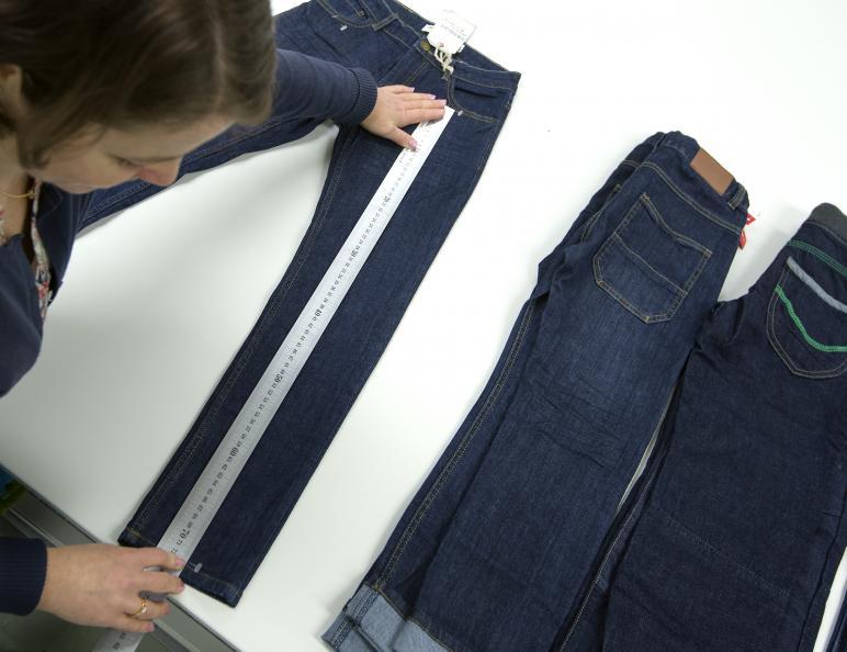 Labbpersonal mäter benet på jeansen med en mätsticka.