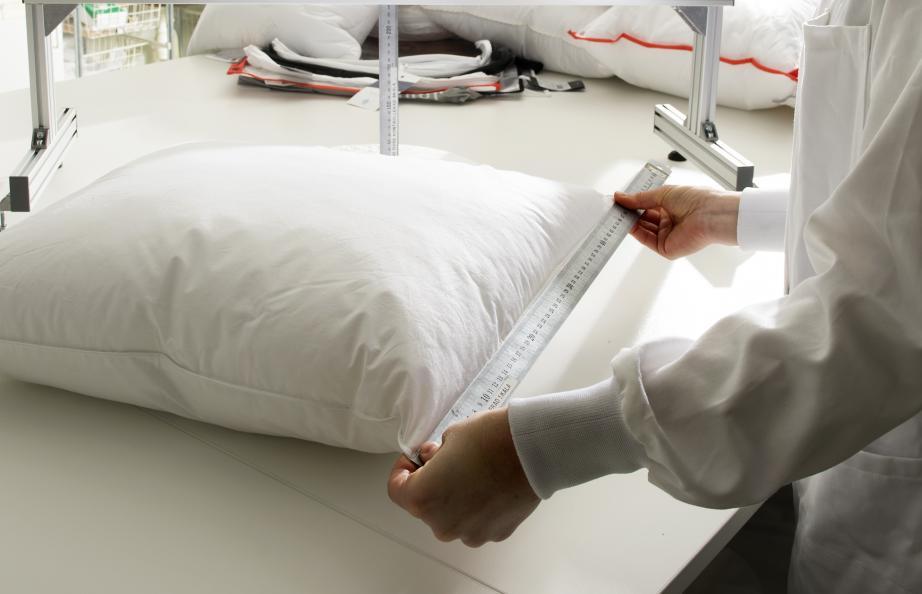 Person mäter längden på kudde med hjälp av linjal.