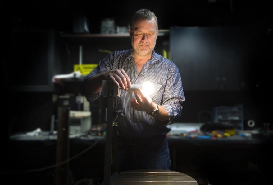 Håkan Skoog skruvar i en led-lampa som lyser upp ett mörkt rum.