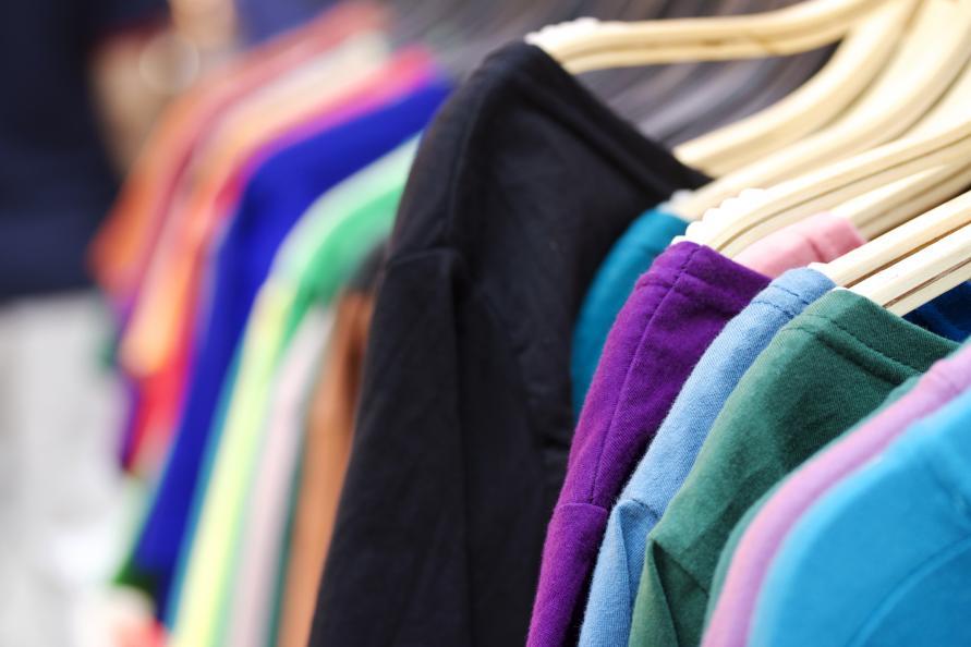 Tröjor i olika färger på galgställning.