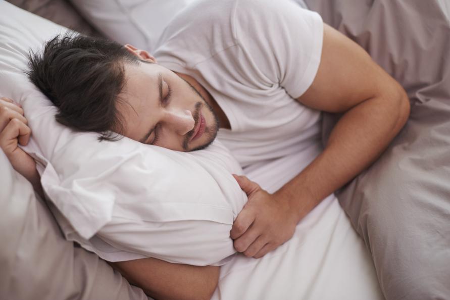En man sover i en säng.