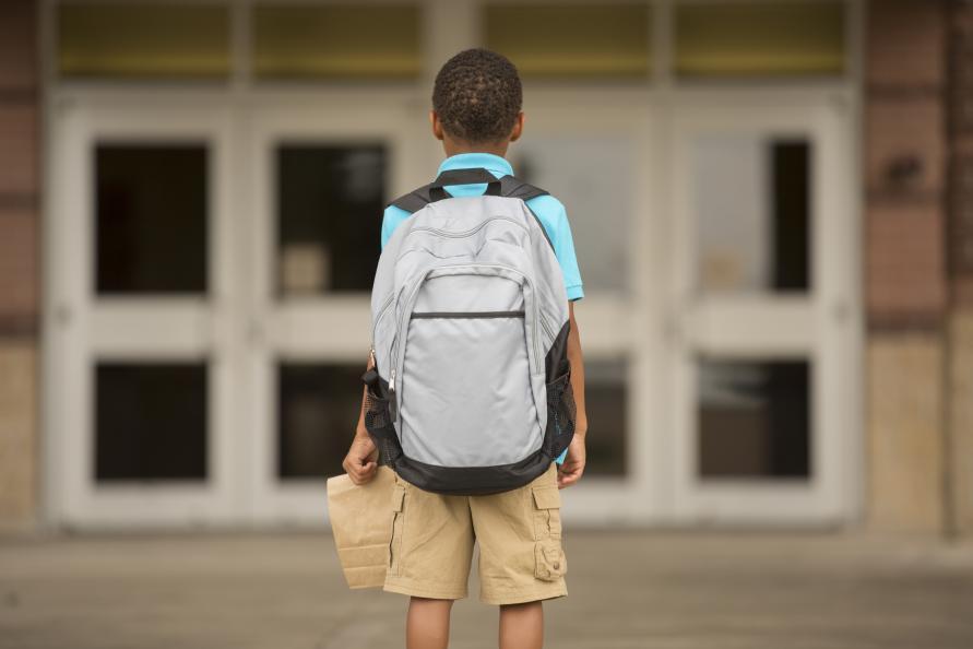 Pojke står framför skola med stor ryggsäck, fotograferad bakifrån.
