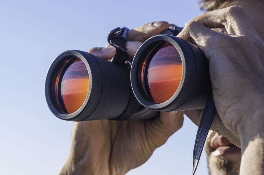 Närbild på person som tittar i kikare
