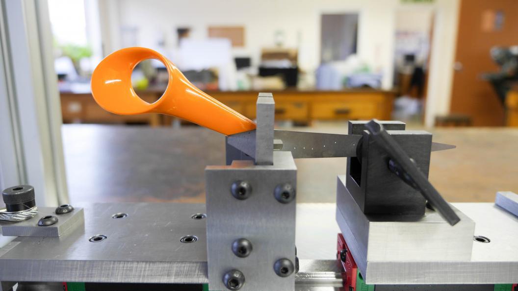 Ett saxblad och dess handtag sitter monterat i en maskin som ska testa handtagets hållbarhet.