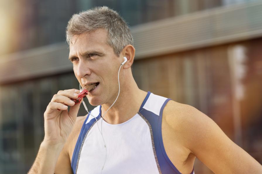Man i träningslinne äter proteinbar.