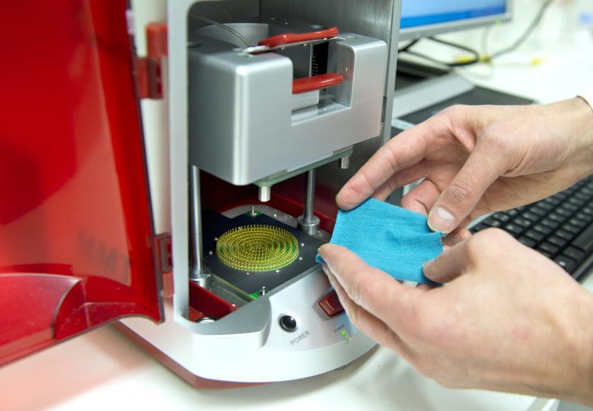 Närbild på händer som lägger en provbit av ett tyg på mätutrustning för att mäta fukttransport.