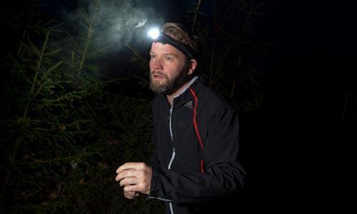 En man springer med en pannlampa i en mörk skog