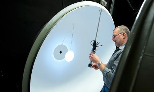 Testledare Håkan Skoogh placerar lamporna i en sfär för att mäta ljusflödet.