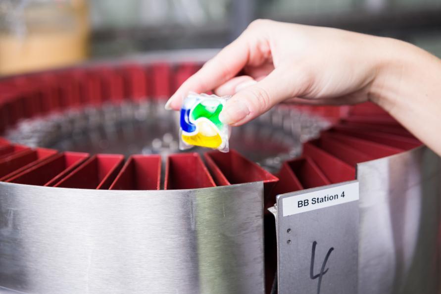 Bioteknologen Nicole Wachtel placerar en diskmedelstablett i  laddningskarusellen av en diskmaskin. Foto  Peter Jülich 3463d4c05ff5e