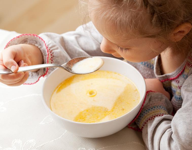 Bild på ett barn som äter soppa.