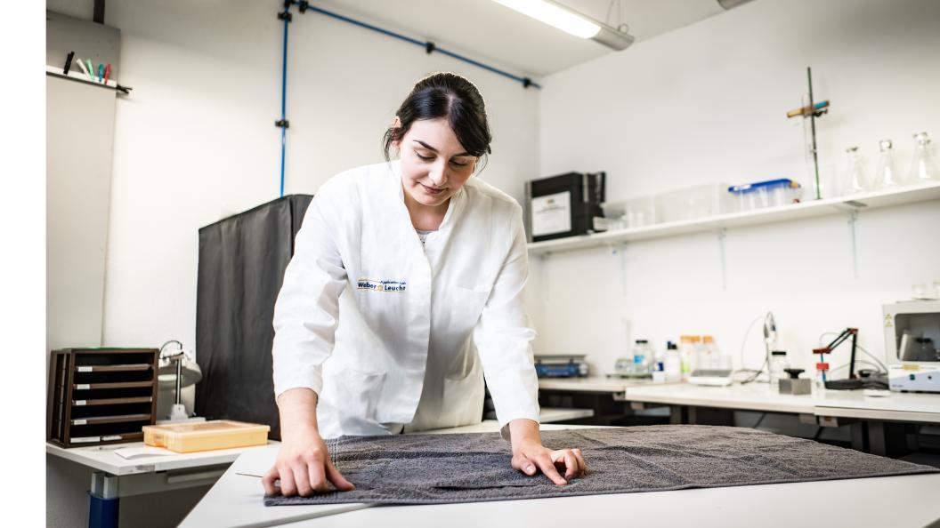 Katarina Röder, statligt certifierad textillaboratorietekniker, mäter hur mycket handdukarna har krympt efter att de har tvättats. Foto: Peter Jülich.