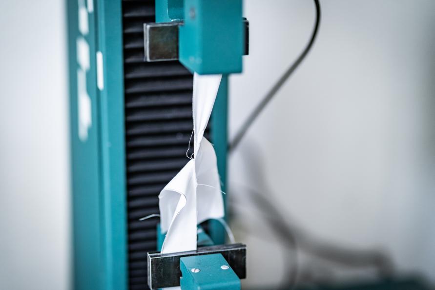 Lakanens förmåga att stå emot rivning testas genom att mäta vilken kraft som behövs för att riva isär tyget från en uppklippt reva. Delprovet visar trådarnas styrka. Foto: Peter Jülich.