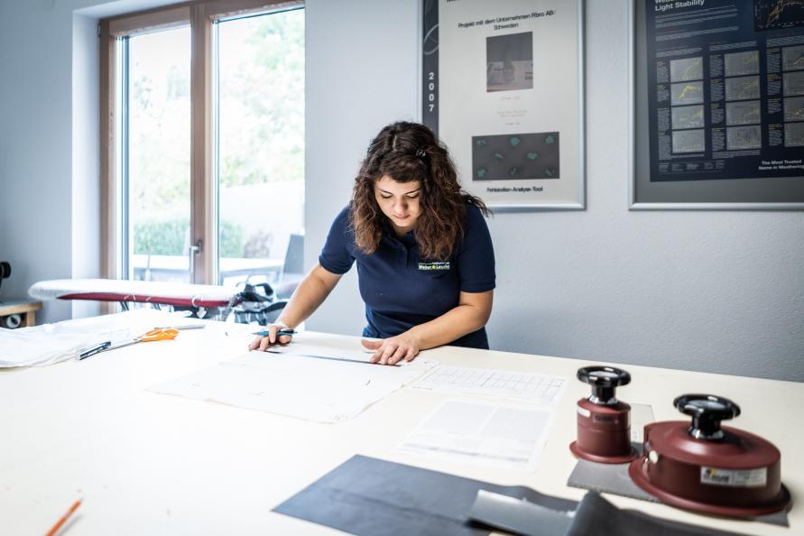Laboratorieteknikern Veronica Occhipinti markerar på ett underlakan hur en provbit ska klippas ut. Foto: Peter Jülich.