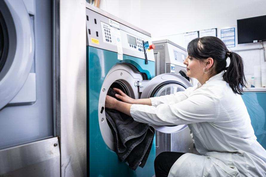 Här lägger Katarina Röder, statligt certifierad textillaboratorietekniker, en handduk i en av labbets tvättmaskiner. Fotograf: Peter Jülich.