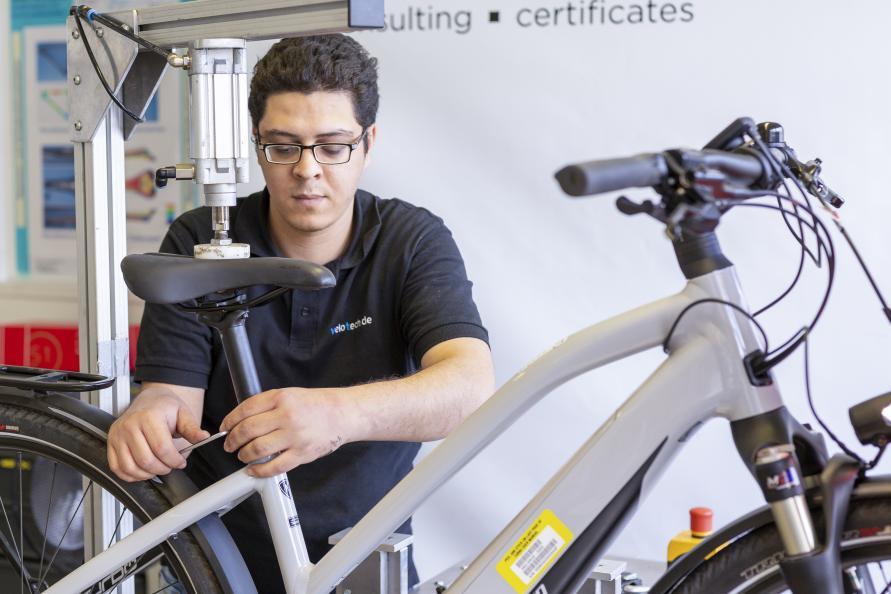 Redouane Bouassaba, testtekniker på velotech.de, justerar elcykeln i testriggen eRig. Här testas räckvidd och prestanda. Foto: Stefan Ernst.