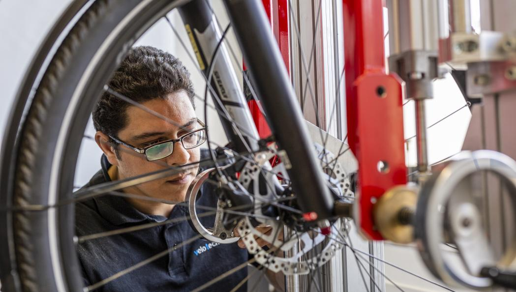 Redouane Bouassaba, testtekniker på velotech.de, fixerar cykelns hjul i testriggen eRig. Foto: Stefan Ernst.