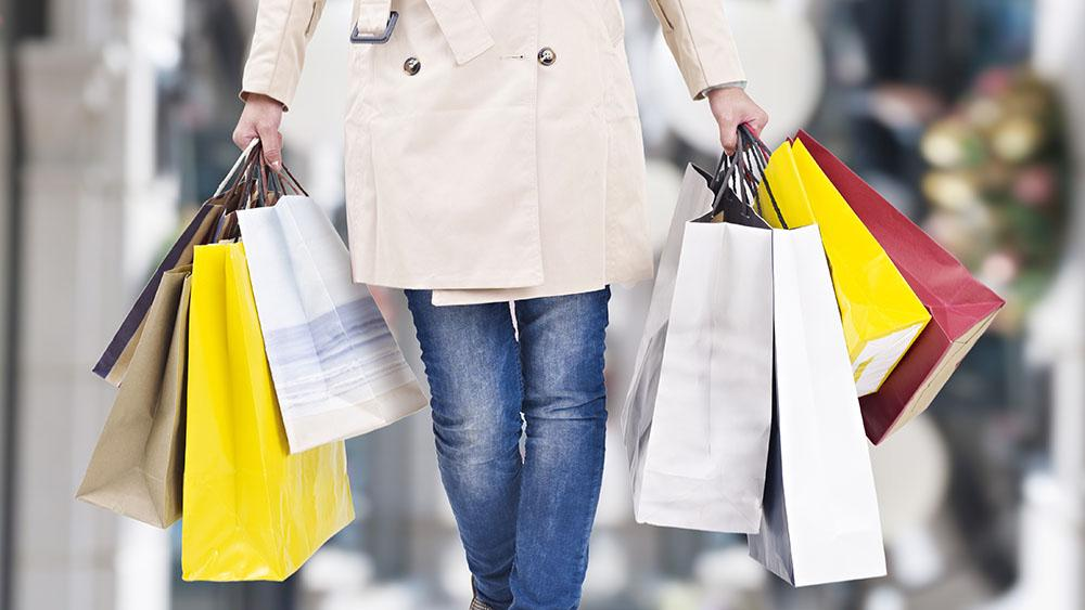 Kvinna med många shoppingkassar i händerna.