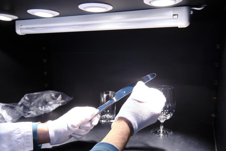 Grå hinna på glas och bestick efter disk bedöms i laboratoriets ljuskammare. Foto: Tobias Meyer