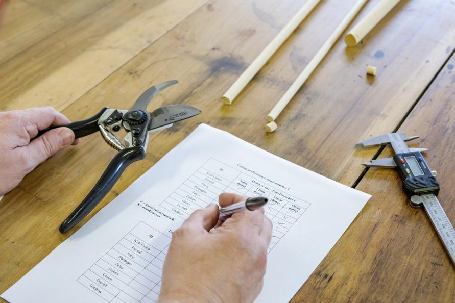 Här dokumenterar en testperson vilka träpinnar den lyckades klippa med varje sekatör. När det kommer till de tjockare pinnarna var det bara med sekatören från Fiskars att alla testpersoner lyckades klippa samtliga pinnar. Bild: Frazer Waller.