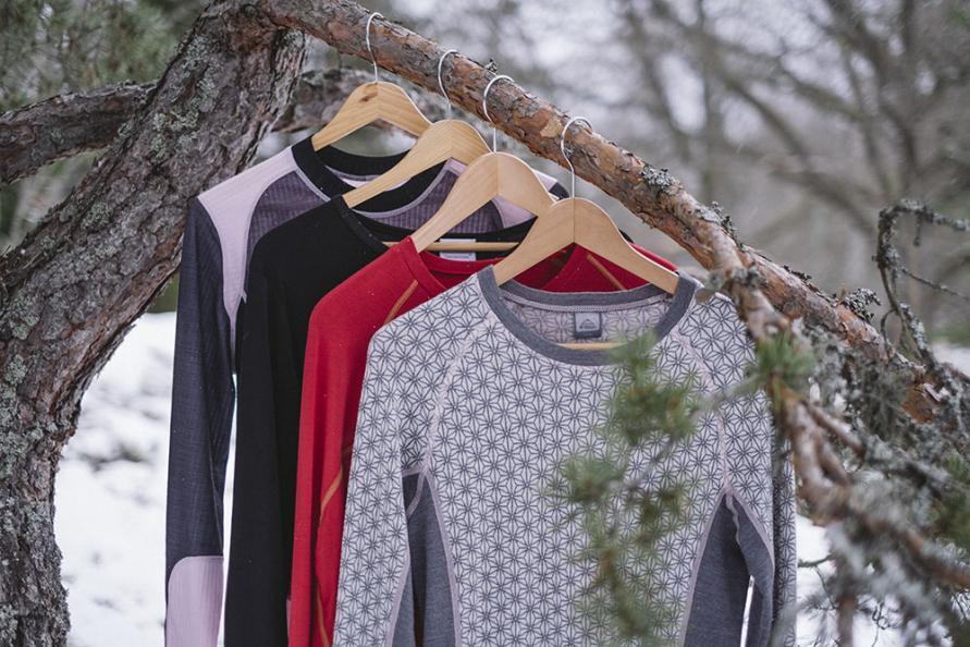 Fyra underställströjor av olika material hänger på en trädgren.