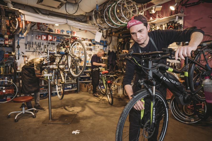 Cykelmekanikern Jovan Lukic justerar bromsarna på en elcykel i verkstaden.
