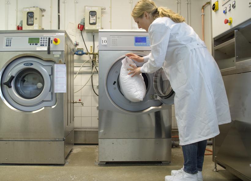 Kvinna stoppar in en kudde i en tvättmaskin.